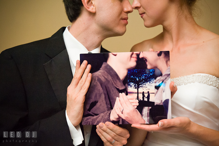 Bride and Groom holding a photo of their engagement session holding a photo of their first date. Riverhouse Pavilion wedding photos at Easton, Eastern Shore, Maryland by photographers of Leo Dj Photography. http://leodjphoto.com
