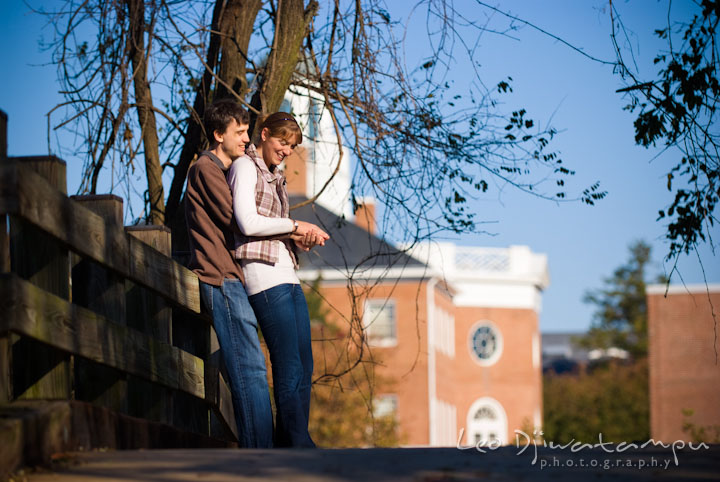 Engaged guy hugging his fiancée on a bridge. Pre-wedding engagement photo session at Washington College and Chestertown, Maryland, by wedding photographer Leo Dj Photography.