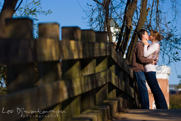 Engaged girl kissed her fiancé on the bridge. Pre-wedding engagement photo session at Washington College and Chestertown, Maryland, by wedding photographer Leo Dj Photography.