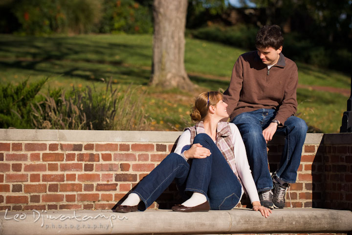 Engaged girl sitting and talking to her fiance. Pre-wedding engagement photo session at Washington College and Chestertown, Maryland, by wedding photographer Leo Dj Photography.