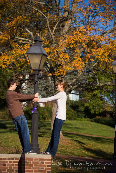 Engaged guy and girl playing by a light pole. Pre-wedding engagement photo session at Washington College and Chestertown, Maryland, by wedding photographer Leo Dj Photography.