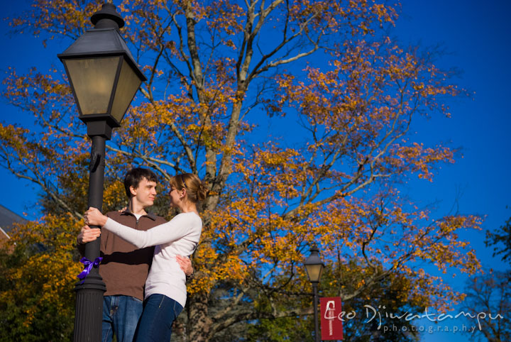 Engaged couple embracing by a light pole. Pre-wedding engagement photo session at Washington College and Chestertown, Maryland, by wedding photographer Leo Dj Photography.