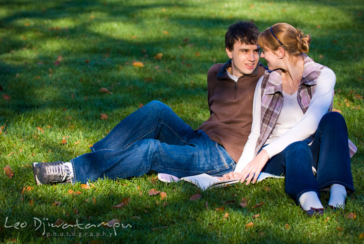 Engaged couple reading a book on the lawn. Pre-wedding engagement photo session at Washington College and Chestertown, Maryland, by wedding photographer Leo Dj Photography.
