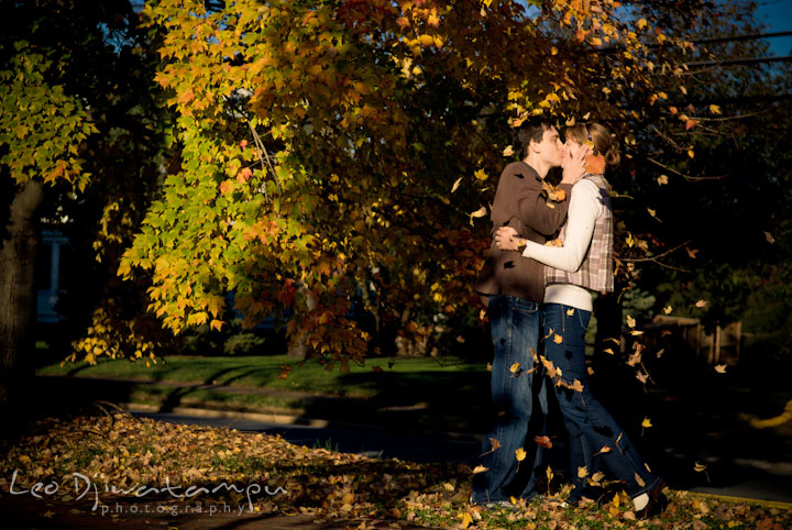 Engaged guy and girl kissing under a tree with falling leaves. Pre-wedding engagement photo session at Washington College and Chestertown, Maryland, by wedding photographer Leo Dj Photography.