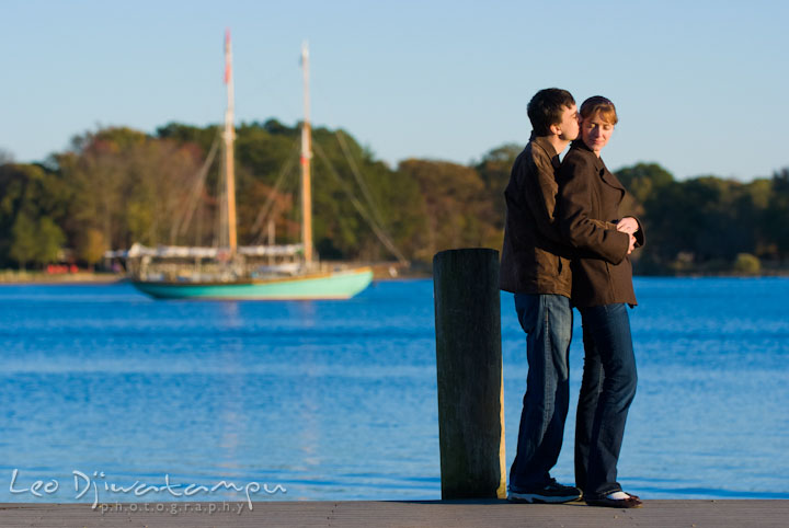 Engaged guy and girl hugging on a pier. Pre-wedding engagement photo session at Washington College and Chestertown, Maryland, by wedding photographer Leo Dj Photography.