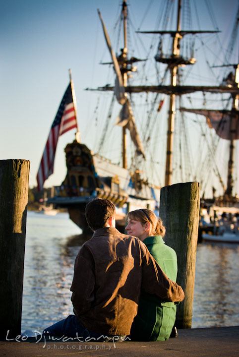 Engaged guy embracing his fiancee, overlooking at an old ship. Pre-wedding engagement photo session at Washington College and Chestertown, Maryland, by wedding photographer Leo Dj Photography.
