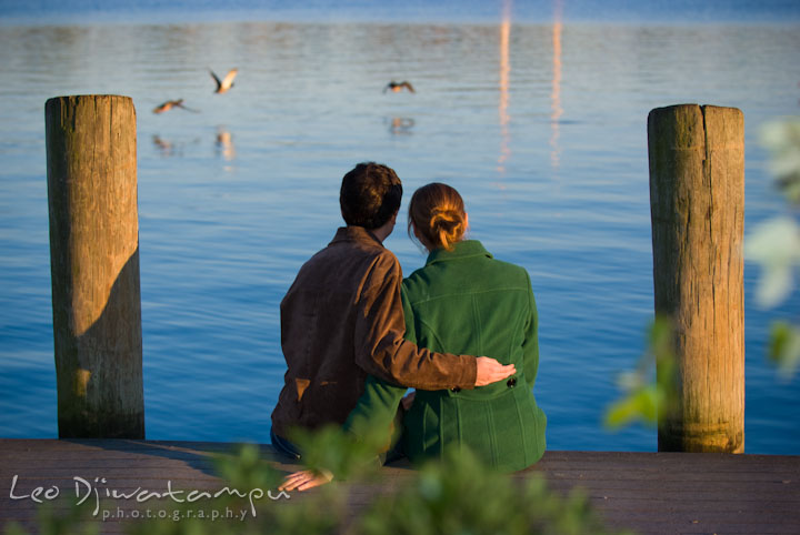 Engaged girl and her fiance enjoying the water view from the pier. Pre-wedding engagement photo session at Washington College and Chestertown, Maryland, by wedding photographer Leo Dj Photography.