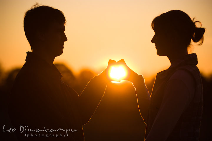Engaged guy and girl making a heart shape around the sun with their hands. Pre-wedding engagement photo session at Washington College and Chestertown, Maryland, by wedding photographer Leo Dj Photography.