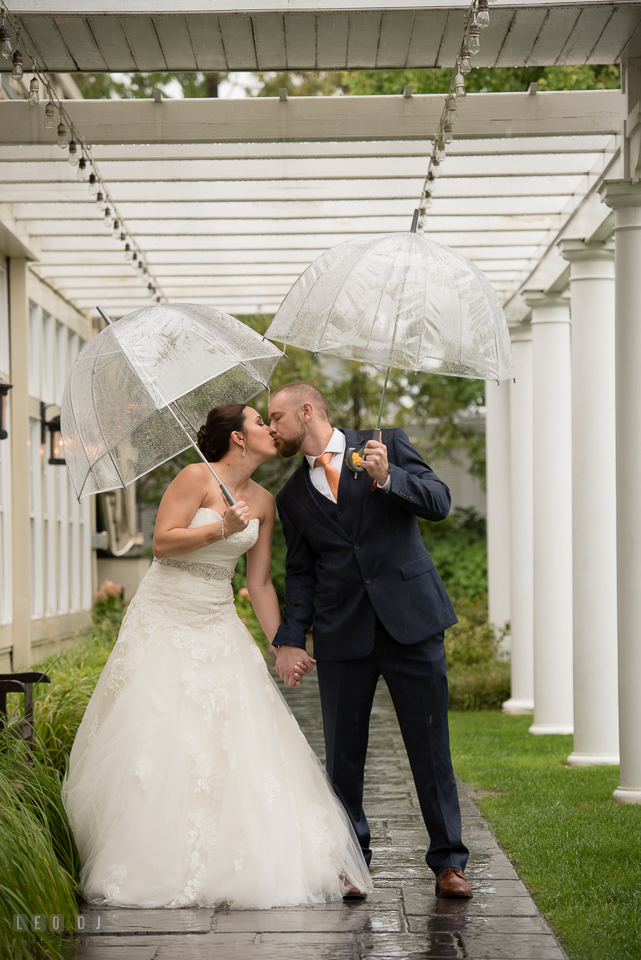 Chesapeake Bay Beach Club Bride and Groom with umbrella kissing under the rain photo by Leo Dj Photography.