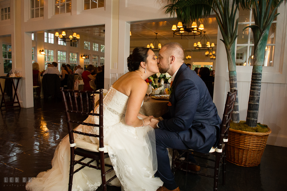 Chesapeake Bay Beach Club Bride and Groom kissing by sweetheart table photo by Leo Dj Photography.