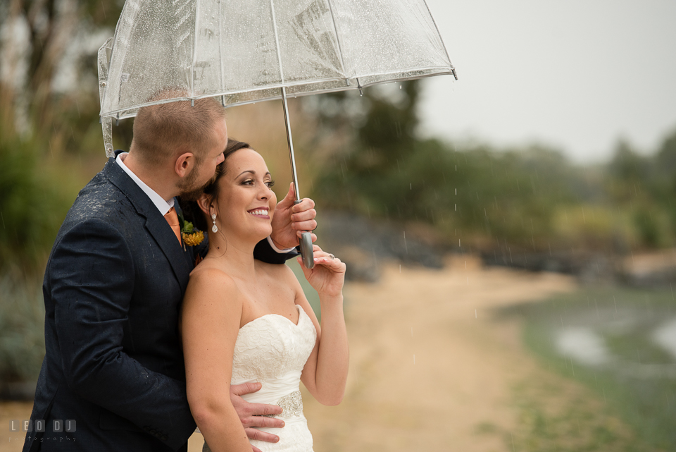 Chesapeake Bay Beach Club Bride and Groom cuddling under the rain photo by Leo Dj Photography.