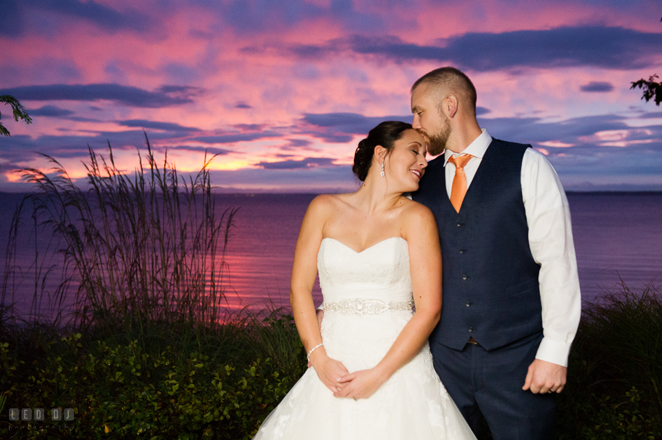 Chesapeake Bay Beach Club Groom kissed Bride by the water under the beautiful sunset sky photo by Leo Dj Photography.