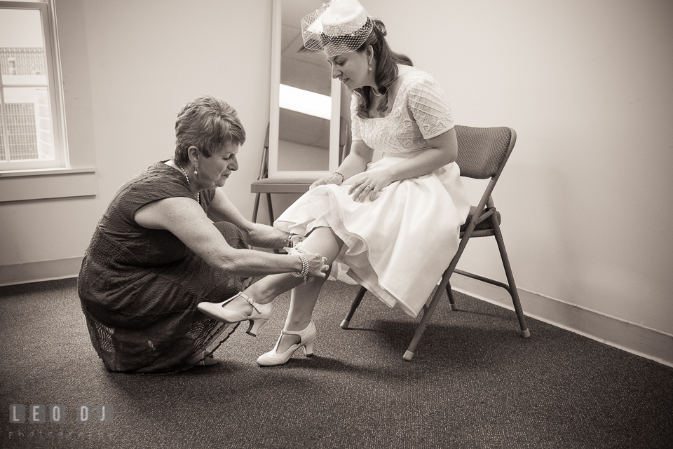 Mother of the Bride putting on garter on daughter's leg. Fisherman's Inn, Safe Harbor Church, Kent Island, Eastern Shore Maryland, wedding reception and ceremony photo, by wedding photographers of Leo Dj Photography. http://leodjphoto.com