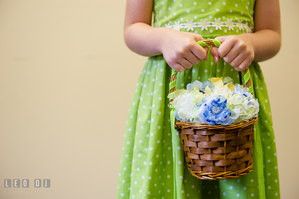 Flower girl holding a basket of fabric flower petals. Fisherman's Inn, Safe Harbor Church, Kent Island, Eastern Shore Maryland, wedding reception and ceremony photo, by wedding photographers of Leo Dj Photography. http://leodjphoto.com