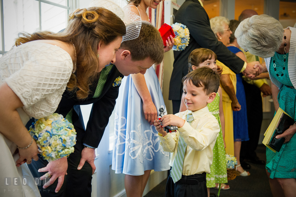 Ring bearer boy showing LEGO truck to Bride and Groom. Fisherman's Inn, Safe Harbor Church, Kent Island, Eastern Shore Maryland, wedding reception and ceremony photo, by wedding photographers of Leo Dj Photography. http://leodjphoto.com