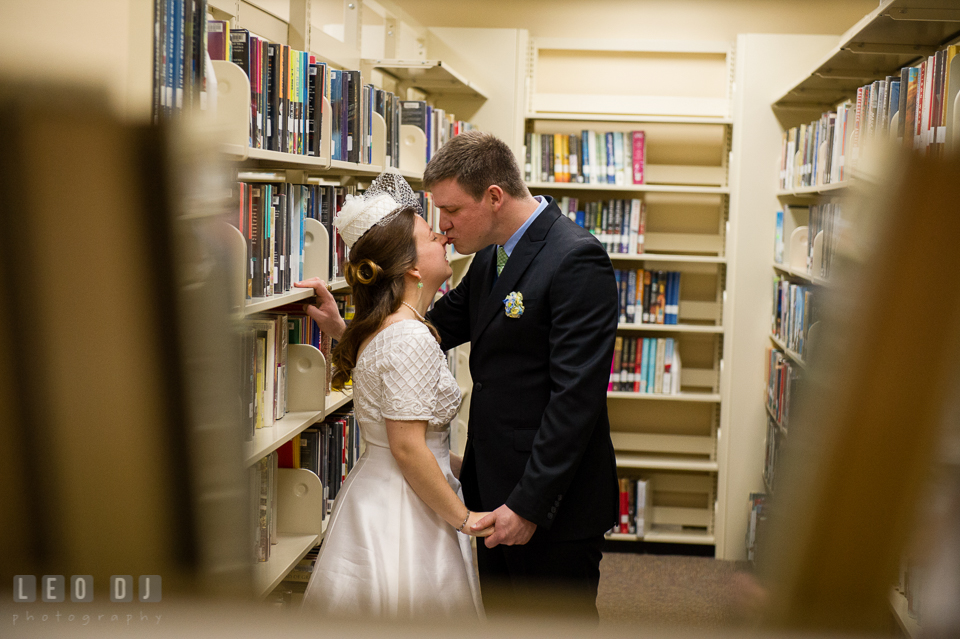 Groom kissing Bride in between rows of book shelves in the library. Fisherman's Inn, Safe Harbor Church, Kent Island, Eastern Shore Maryland, wedding reception and ceremony photo, by wedding photographers of Leo Dj Photography. http://leodjphoto.com