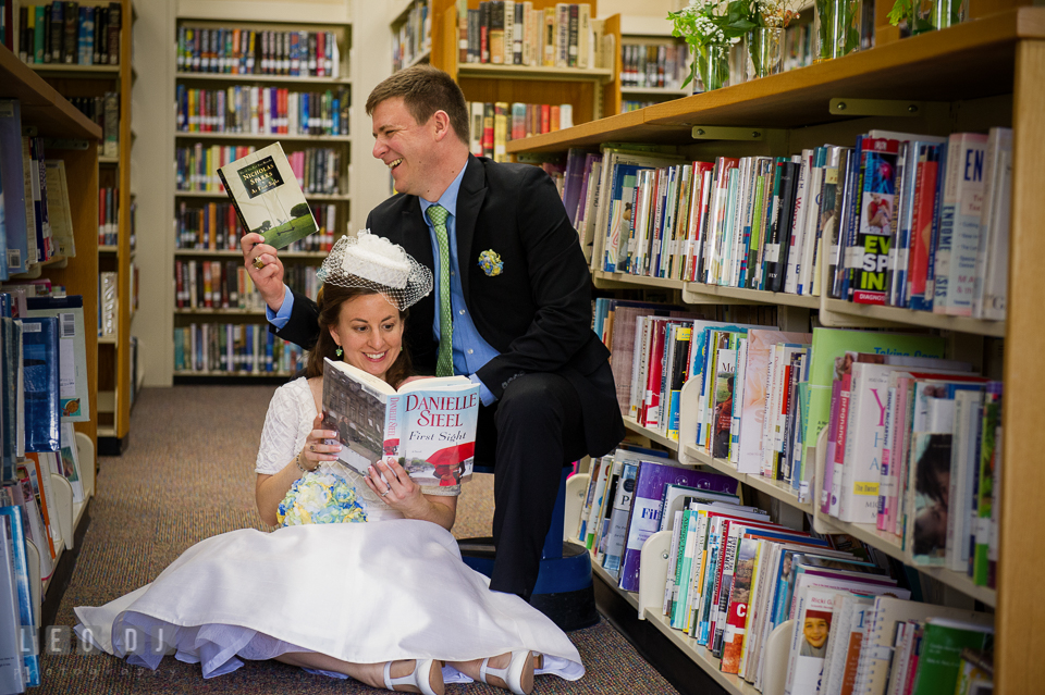 Bride and Groom sitting and reading books together in the library. Fisherman's Inn, Safe Harbor Church, Kent Island, Eastern Shore Maryland, wedding reception and ceremony photo, by wedding photographers of Leo Dj Photography. http://leodjphoto.com