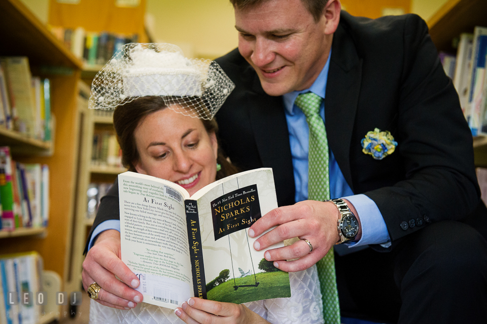 Bride and Groom reading a book and smiling. Fisherman's Inn, Safe Harbor Church, Kent Island, Eastern Shore Maryland, wedding reception and ceremony photo, by wedding photographers of Leo Dj Photography. http://leodjphoto.com