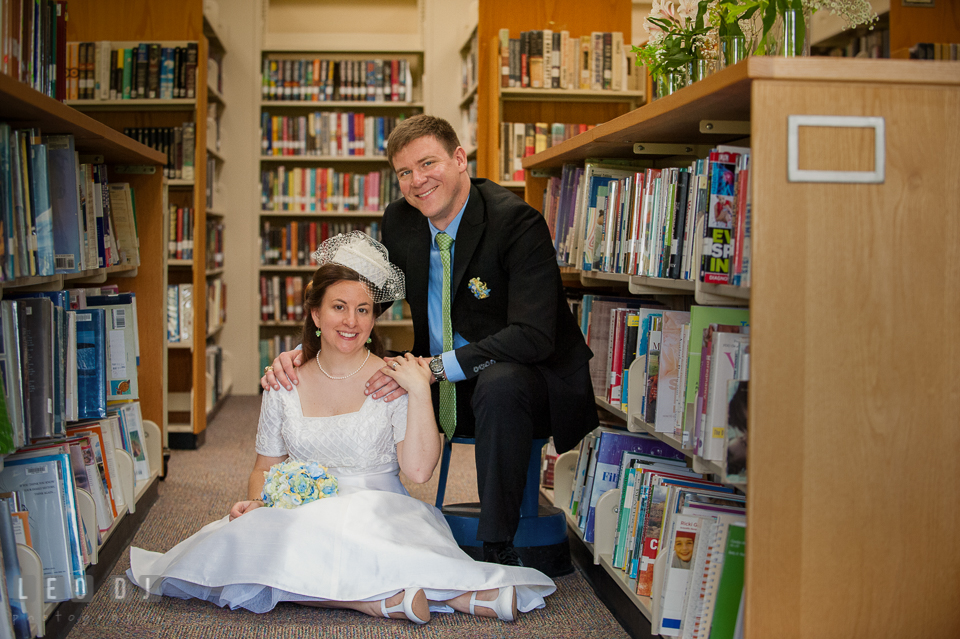 Bride and Groom posing by the books in the library. Fisherman's Inn, Safe Harbor Church, Kent Island, Eastern Shore Maryland, wedding reception and ceremony photo, by wedding photographers of Leo Dj Photography. http://leodjphoto.com