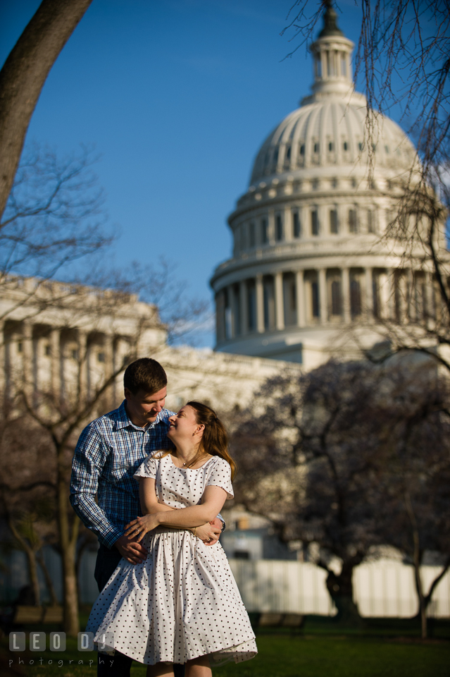 Engaged guy hugging his fiancée at the West lawn of the Capitol Hill . Washington DC pre-wedding engagement photo session at the Capitol Hill and the Mall, by wedding photographers of Leo Dj Photography. http://leodjphoto.com