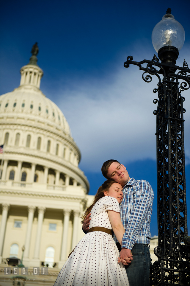 Engaged couple cuddling together in front of the Captiol Hill . Washington DC pre-wedding engagement photo session at the Capitol Hill and the Mall, by wedding photographers of Leo Dj Photography. http://leodjphoto.com