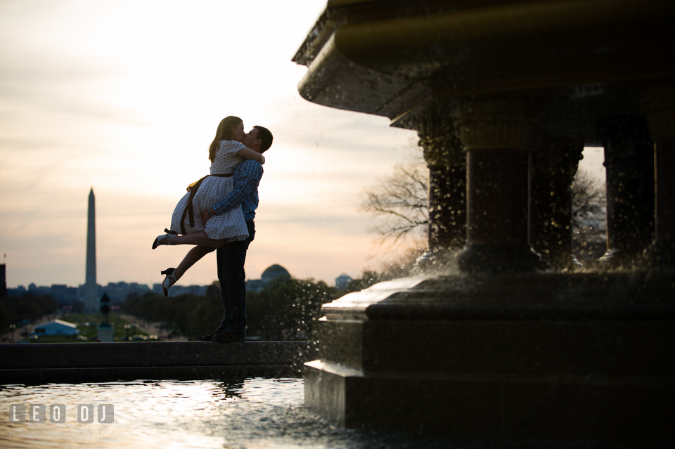 Engaged couple kissing by the water fountain with the Washington Monument in the background during sunset. Washington DC pre-wedding engagement photo session at the Capitol Hill and the Mall, by wedding photographers of Leo Dj Photography. http://leodjphoto.com