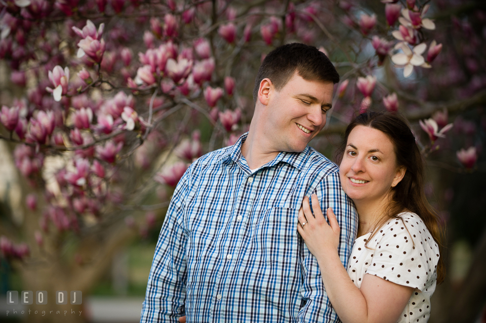 Engaged girl holding her fiancé by a blooming magnolia tree. Washington DC pre-wedding engagement photo session at the Capitol Hill and the Mall, by wedding photographers of Leo Dj Photography. http://leodjphoto.com