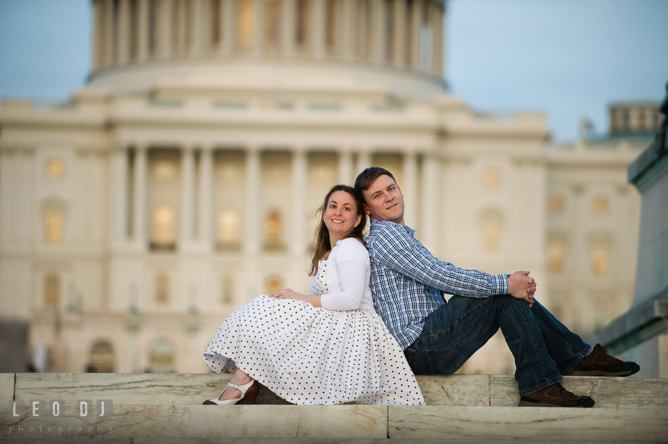 Engaged girl sitting back to back with her fiancé by the stairs at the Capitol Hill. Washington DC pre-wedding engagement photo session at the Capitol Hill and the Mall, by wedding photographers of Leo Dj Photography. http://leodjphoto.com