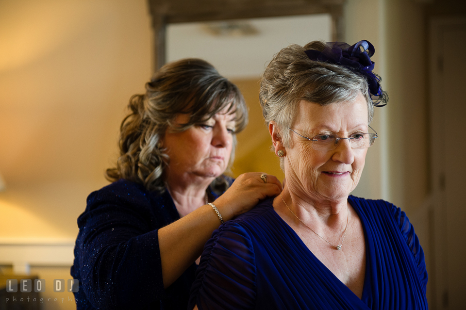Mother of the Groom helping Mother of Bride putting on the necklace. Kent Island Maryland Chesapeake Bay Beach Club wedding photo, by wedding photographers of Leo Dj Photography. http://leodjphoto.com