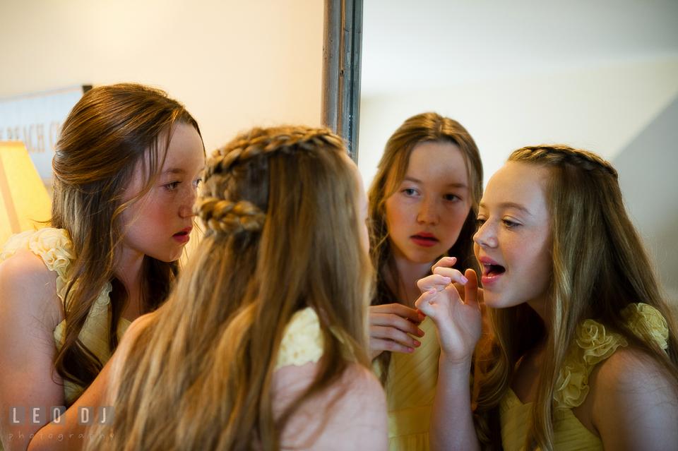 Two junior bridesmaids looking at the mirror checking their make up. Kent Island Maryland Chesapeake Bay Beach Club wedding photo, by wedding photographers of Leo Dj Photography. http://leodjphoto.com