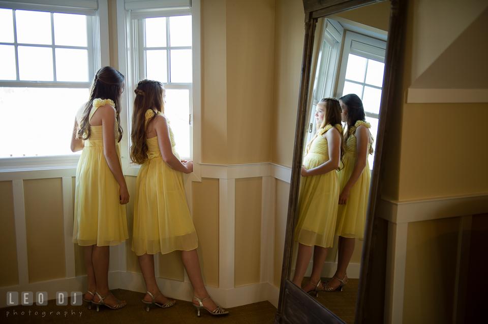 Two junior bridesmaids girls looking out at the window. Kent Island Maryland Chesapeake Bay Beach Club wedding photo, by wedding photographers of Leo Dj Photography. http://leodjphoto.com