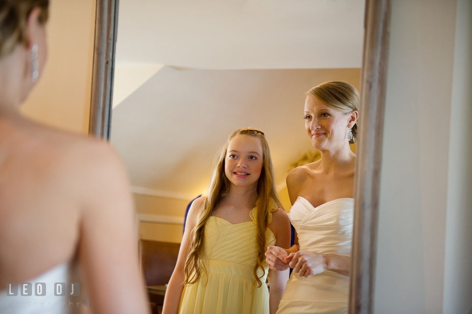 Bride and her niece looking at the mirror and smiling. Kent Island Maryland Chesapeake Bay Beach Club wedding photo, by wedding photographers of Leo Dj Photography. http://leodjphoto.com