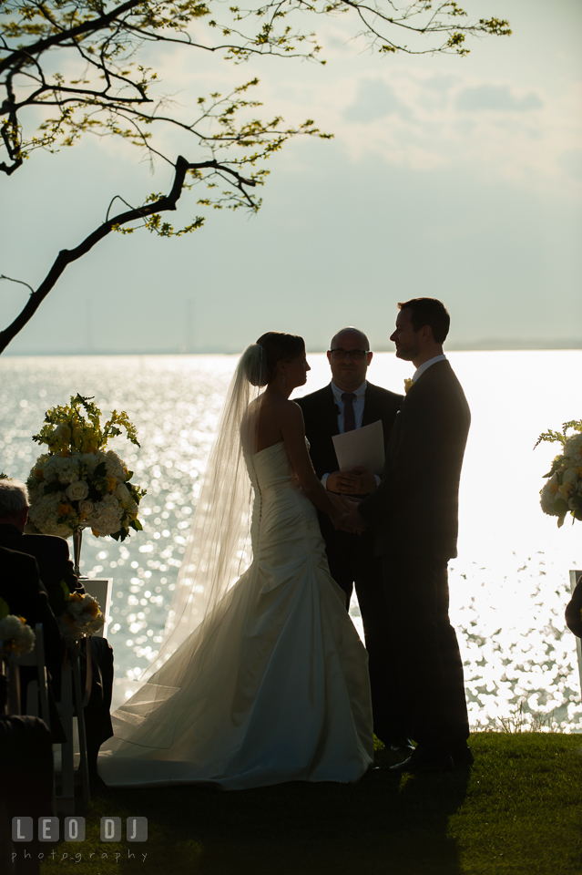 Silhouette of Bride and Groom during the ceremony with water in the background. Kent Island Maryland Chesapeake Bay Beach Club wedding photo, by wedding photographers of Leo Dj Photography. http://leodjphoto.com