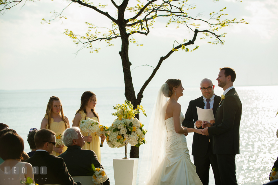 Bride and Groom looking at each other during the ceremony watched by their junior bridesmaids. Kent Island Maryland Chesapeake Bay Beach Club wedding photo, by wedding photographers of Leo Dj Photography. http://leodjphoto.com