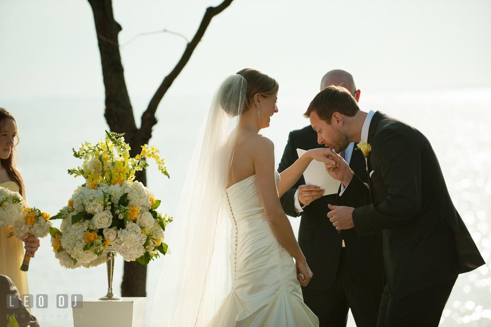 Groom kissing Bride's hand during the ceremony. Kent Island Maryland Chesapeake Bay Beach Club wedding photo, by wedding photographers of Leo Dj Photography. http://leodjphoto.com