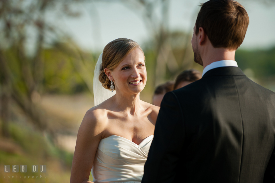 Bride smiling looking at Groom during the vow at the ceremony. Kent Island Maryland Chesapeake Bay Beach Club wedding photo, by wedding photographers of Leo Dj Photography. http://leodjphoto.com