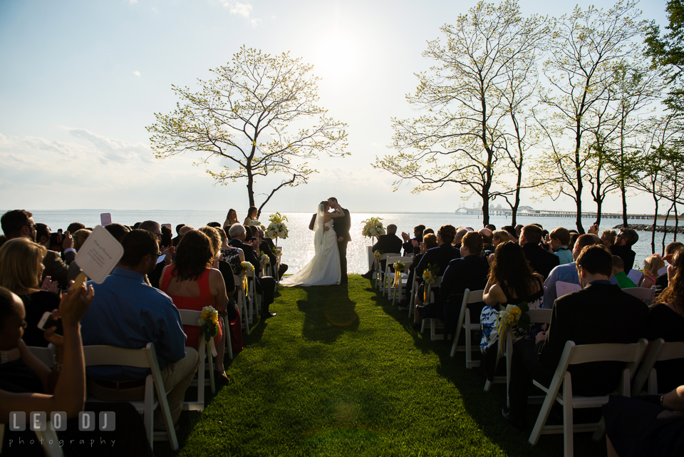 Bride and Groom kissing during the ceremony with the water and the Chesapeake Bay Bridge in the background. Kent Island Maryland Chesapeake Bay Beach Club wedding photo, by wedding photographers of Leo Dj Photography. http://leodjphoto.com