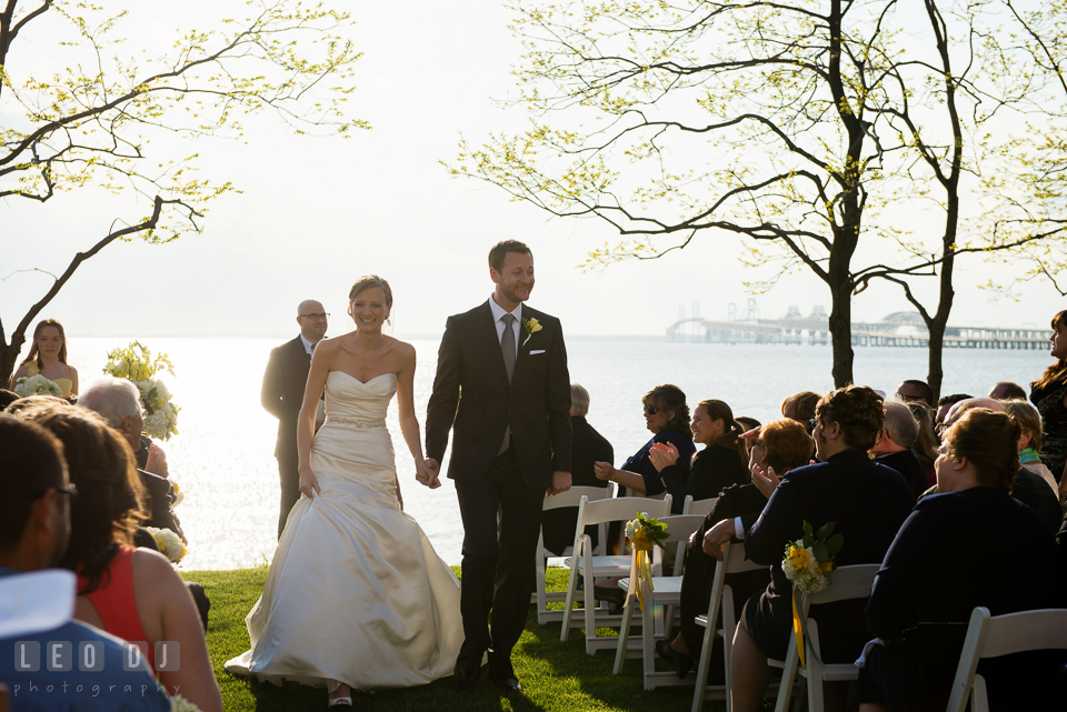 Bride and Groom holding hands walking out the aisle during processional. Kent Island Maryland Chesapeake Bay Beach Club wedding photo, by wedding photographers of Leo Dj Photography. http://leodjphoto.com