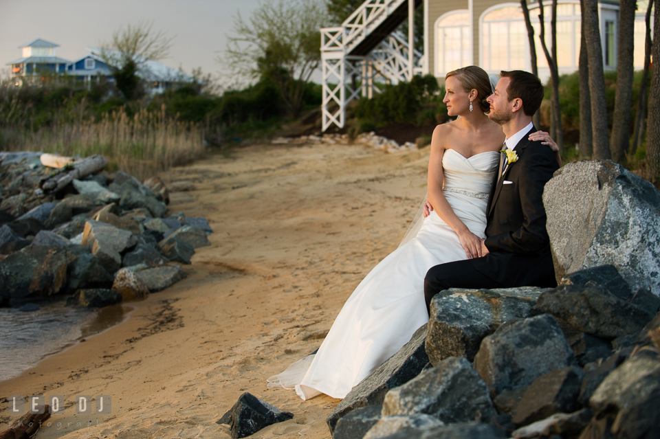 Bride and Groom at the beach sitting together on the rocks overlooking at the water. Kent Island Maryland Chesapeake Bay Beach Club wedding photo, by wedding photographers of Leo Dj Photography. http://leodjphoto.com