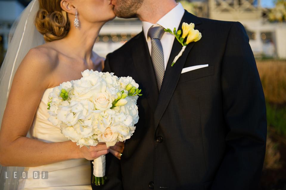 Bride holding her flower bouquet kissing the groom. Kent Island Maryland Chesapeake Bay Beach Club wedding photo, by wedding photographers of Leo Dj Photography. http://leodjphoto.com