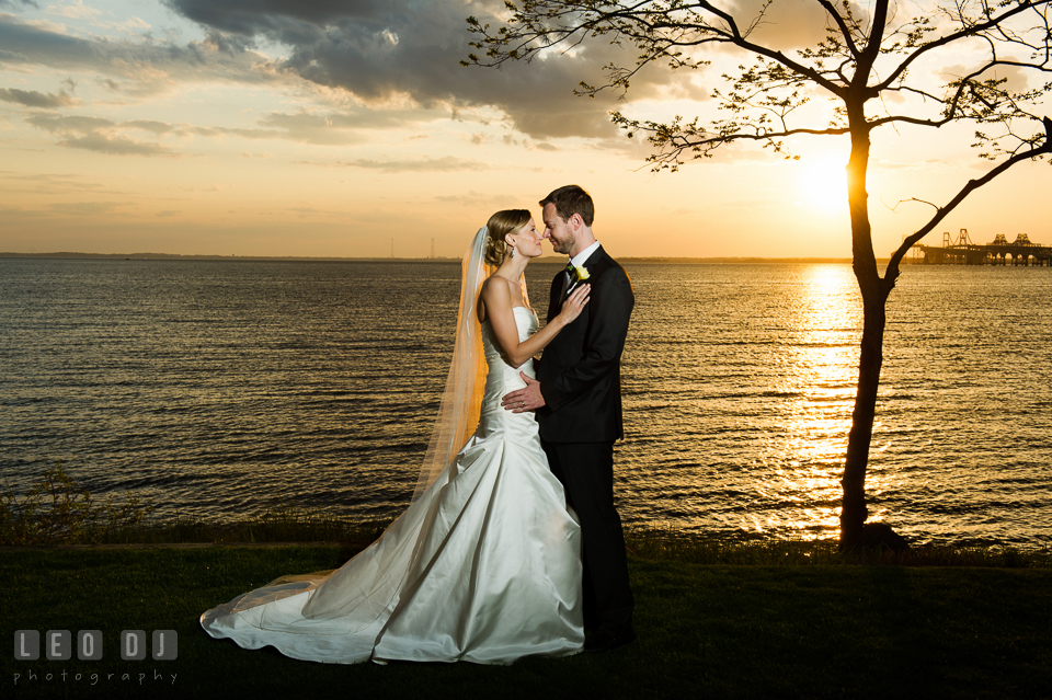 Bride and Groom embracing each other with the sunset on the water in the background. Kent Island Maryland Chesapeake Bay Beach Club wedding photo, by wedding photographers of Leo Dj Photography. http://leodjphoto.com