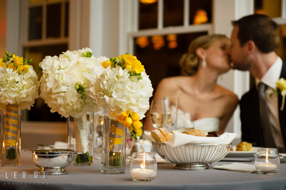 Sweetheart table with the flower bouquets with the Bride and Groom kissing in the background. Kent Island Maryland Chesapeake Bay Beach Club wedding photo, by wedding photographers of Leo Dj Photography. http://leodjphoto.com