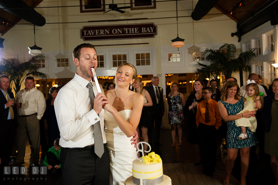 Groom licking cake icing from knife during cake cutting. Kent Island Maryland Chesapeake Bay Beach Club wedding photo, by wedding photographers of Leo Dj Photography. http://leodjphoto.com