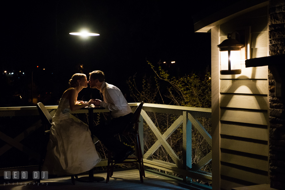 Bride and Groom sitting by a table at an outdoor terrace in the evening. Kent Island Maryland Chesapeake Bay Beach Club wedding photo, by wedding photographers of Leo Dj Photography. http://leodjphoto.com