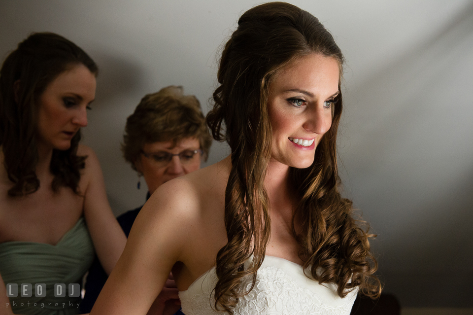 Bride smiling while Mother and Maid of Honor helps button up the wedding dress. Historic Inns of Annapolis Maryland, Governor Calvert House wedding, by wedding photographers of Leo Dj Photography. http://leodjphoto.com