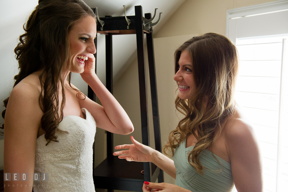 Bride putting on her earring and laughing with her bridesmaid. Historic Inns of Annapolis Maryland, Governor Calvert House wedding, by wedding photographers of Leo Dj Photography. http://leodjphoto.com