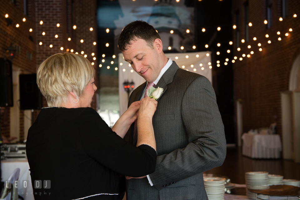 Mother of Groom putting on boutonniere on her son's jacket. Historic Inns of Annapolis Maryland, Governor Calvert House wedding, by wedding photographers of Leo Dj Photography. http://leodjphoto.com