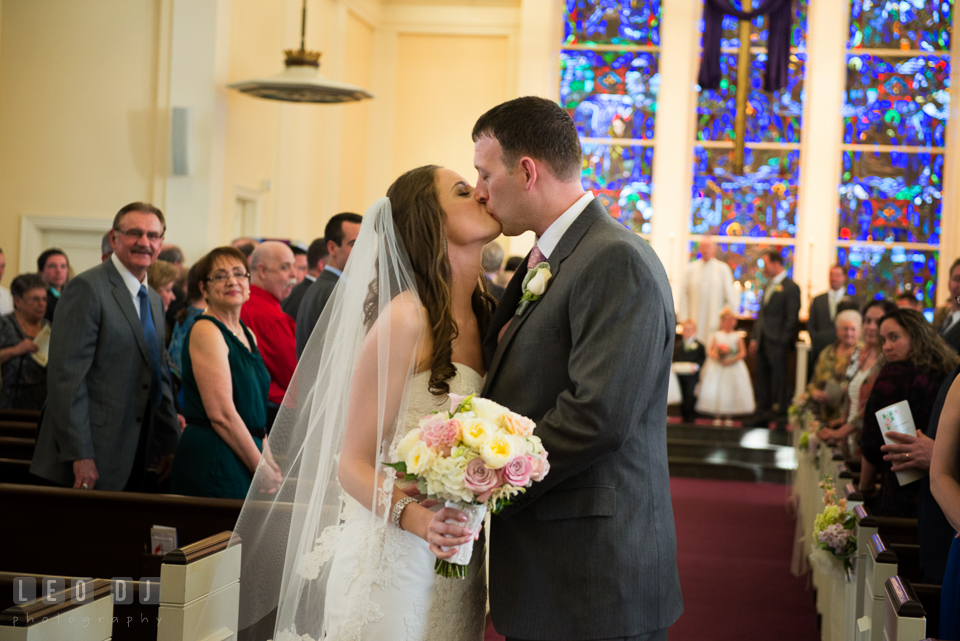 Bride and Groom kissing during ceremony processional at Calvary United Methodist Church. Historic Inns of Annapolis Maryland, Governor Calvert House wedding, by wedding photographers of Leo Dj Photography. http://leodjphoto.com