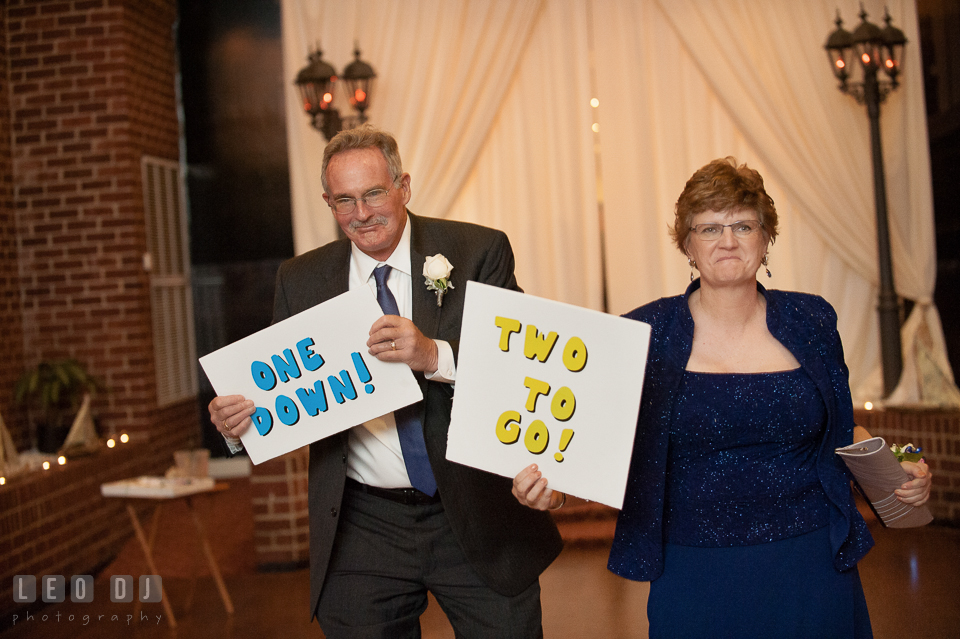 Mother and Father of Bride during the introduction holding signs of One Down, Two to Go. Historic Inns of Annapolis Maryland, Governor Calvert House wedding, by wedding photographers of Leo Dj Photography. http://leodjphoto.com