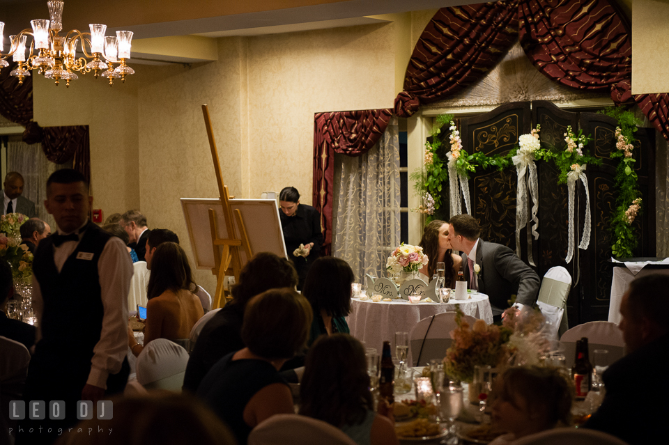 Bride and Groom kissing at their sweetheart table after glass clinking from guests while the painter Patricia Bennet paints the room. Historic Inns of Annapolis Maryland, Governor Calvert House wedding, by wedding photographers of Leo Dj Photography. http://leodjphoto.com